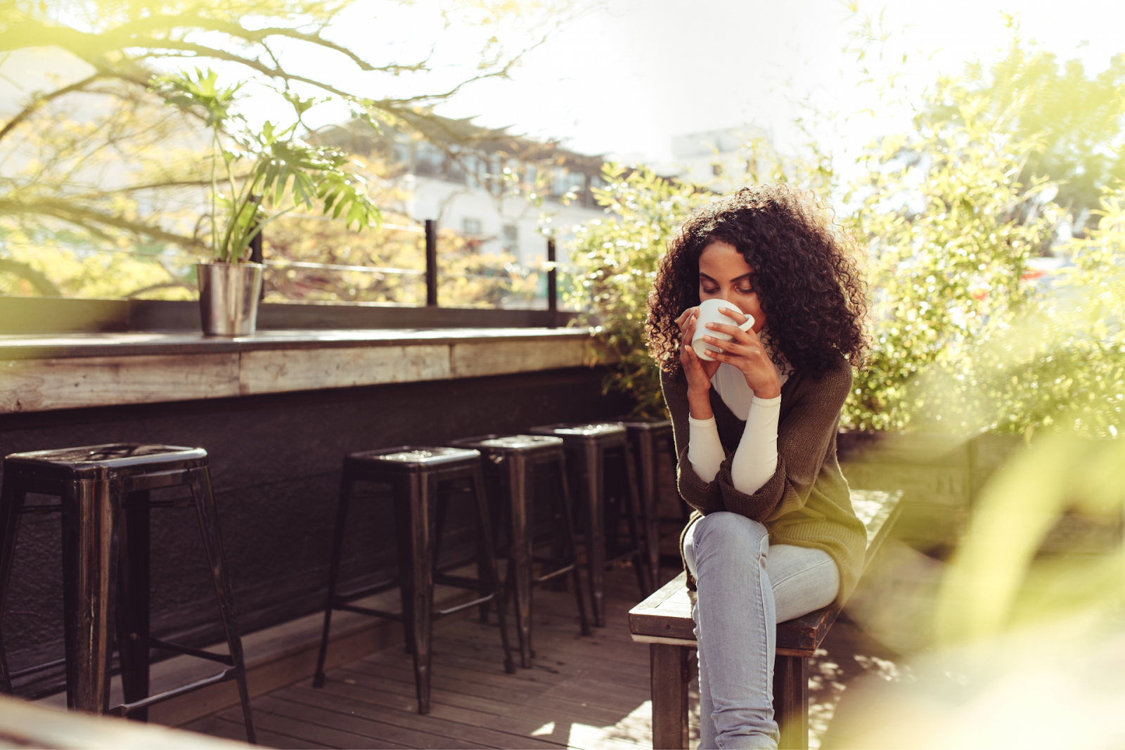 happy woman sipping on a cup of coffee