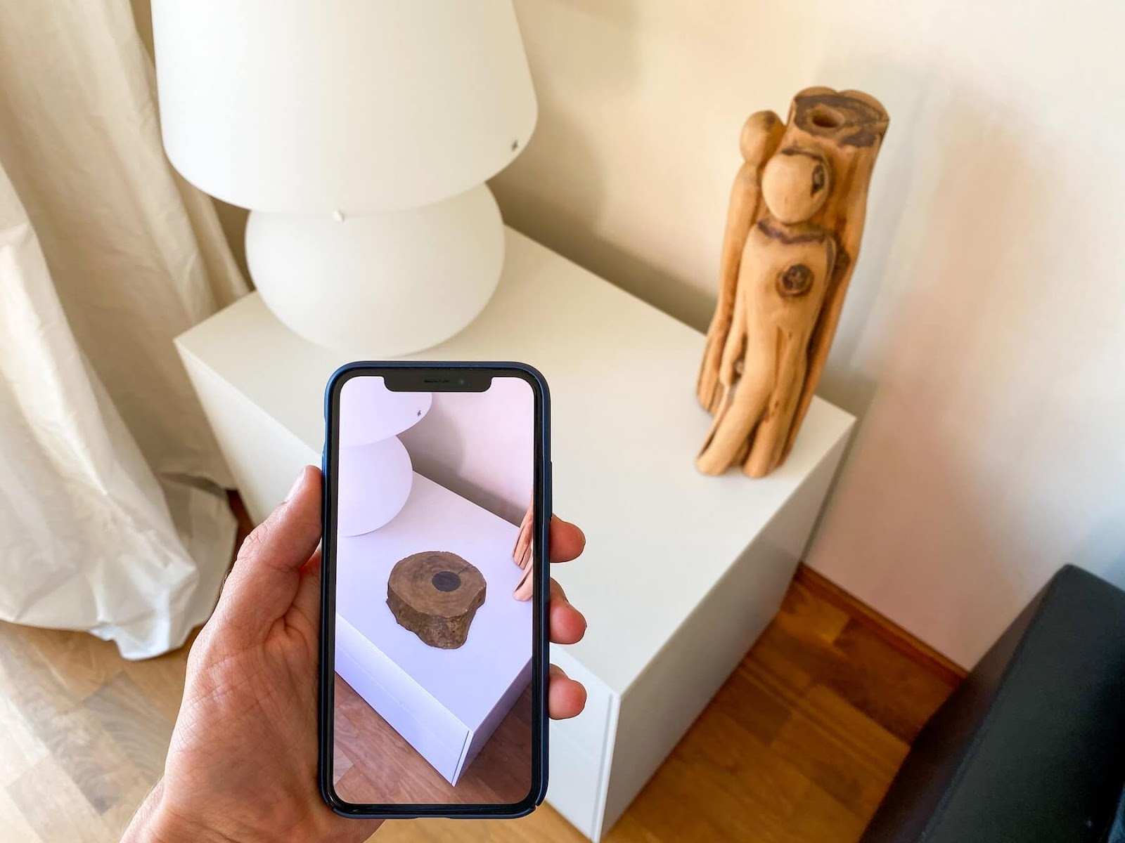 person using augmented reality on their phone to see a piece of furniture in their room