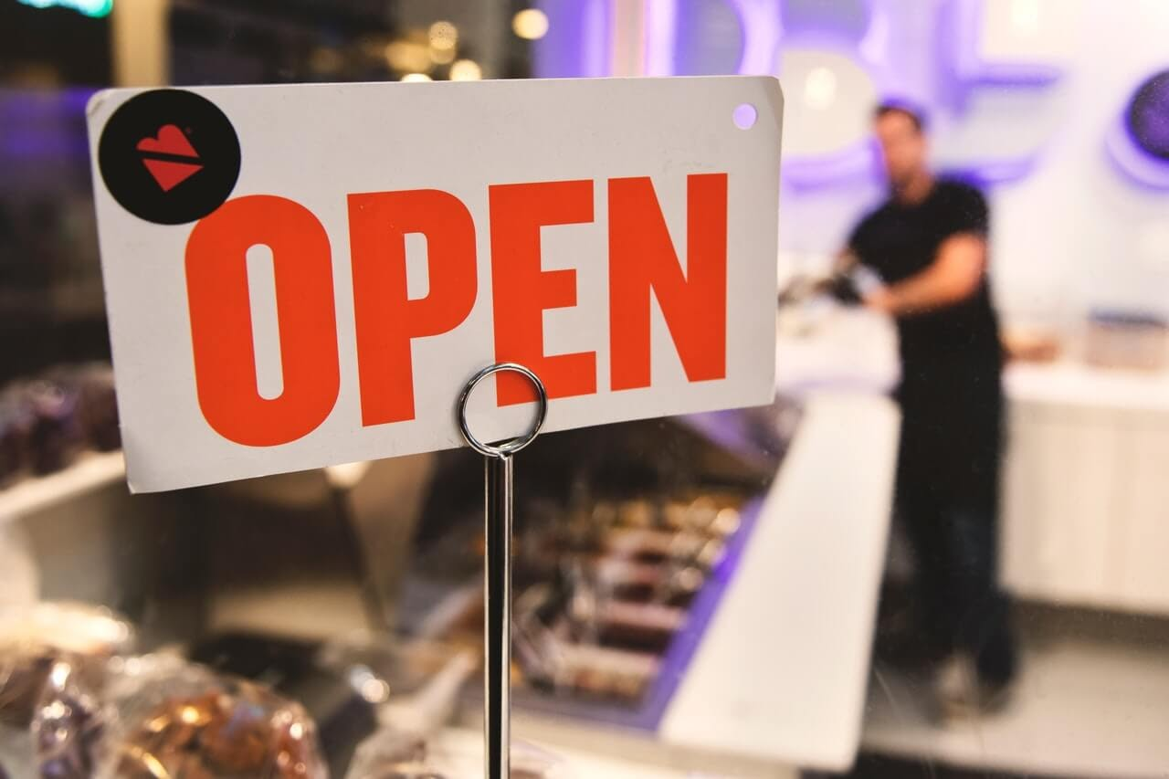 open sign in store focus man in background salesperson