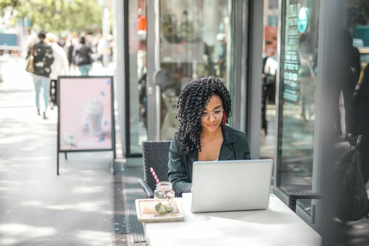 woman outside on laptop having lunch on busy street during the day