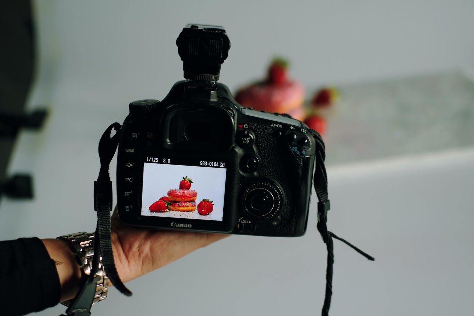 a hand holding a digital camera showing the photo it just took of strawberries and other food.