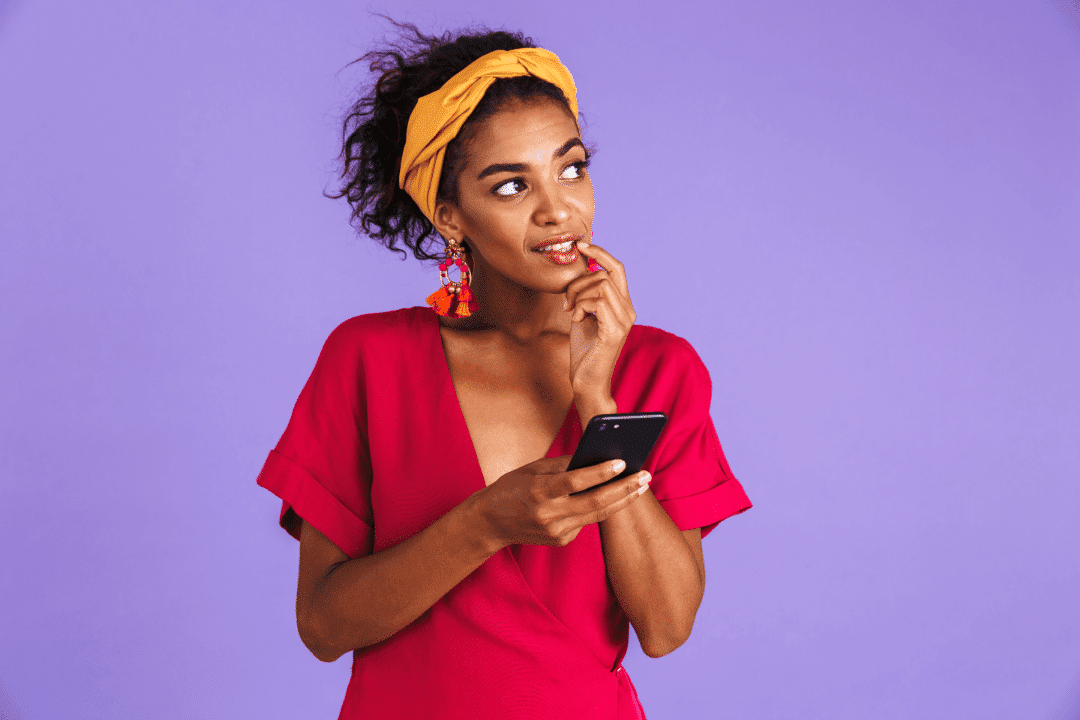 young woman looking off into distance questioning on cell phone purple background