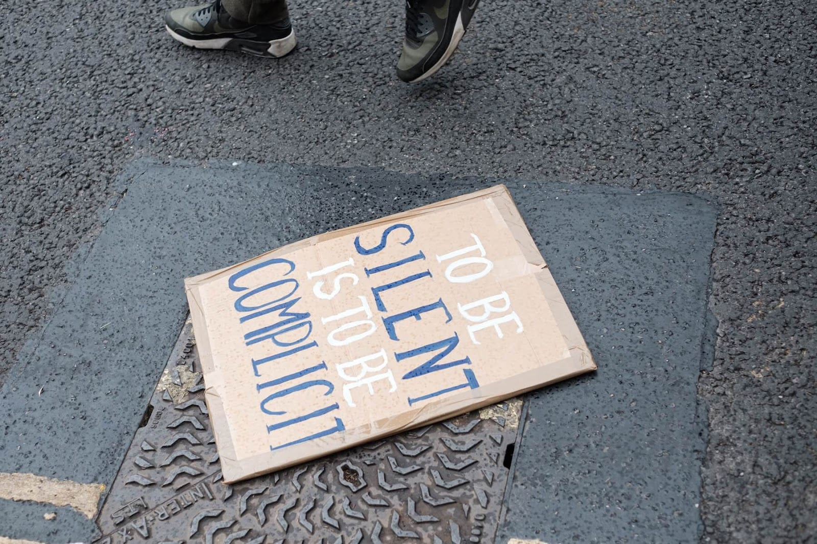 """a protestor sign on the ground that reads """"to be silent is to be complicit"""""""