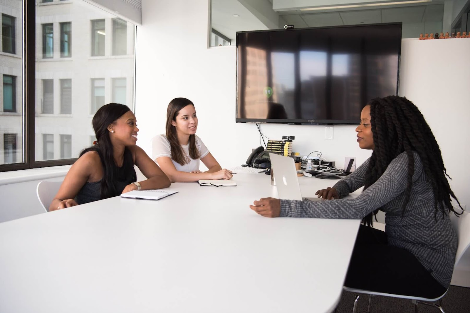 three people sitting around a conference table brainstorming ideas.