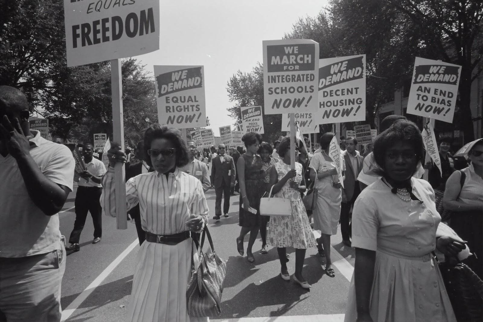 protestors for racial integration march down the street holding the signs in the 1960's.