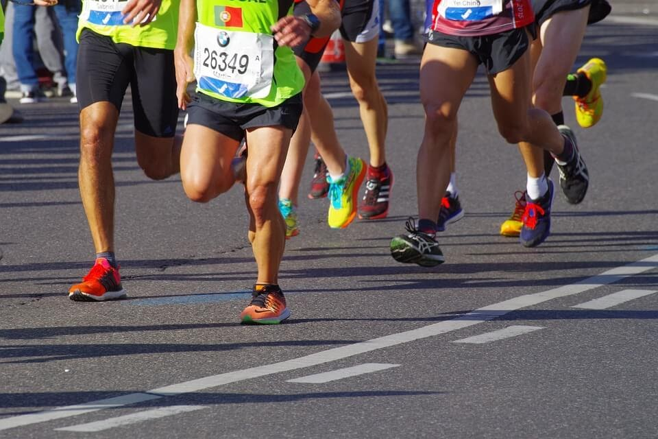 the feet of several marathon contestants running down the street in athletic shoes