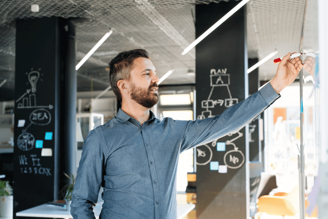 man writing on whiteboard in new looking office