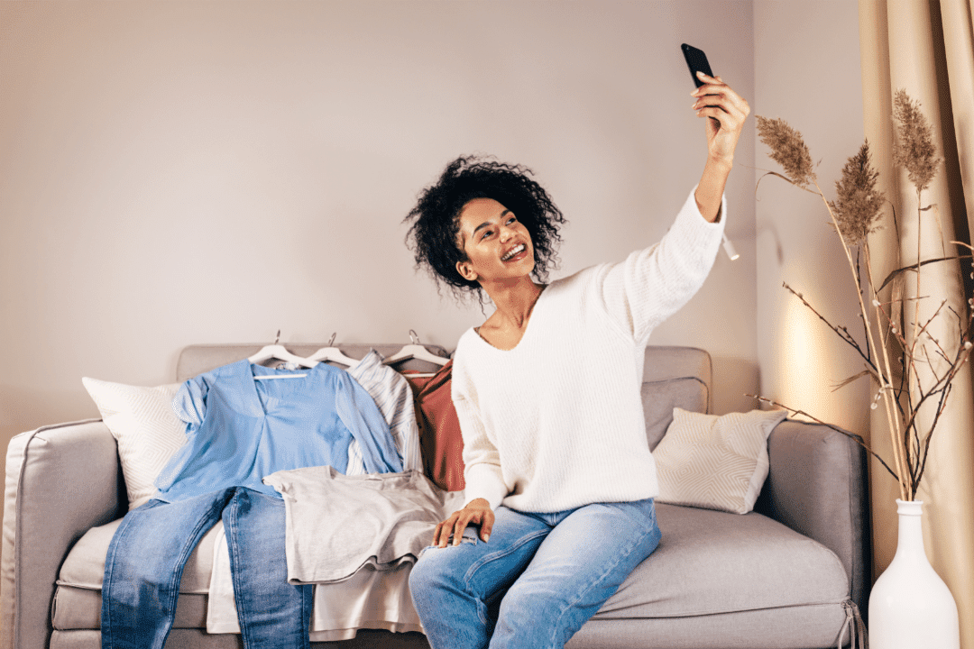 young woman taking a selfie with clothing haul in living room