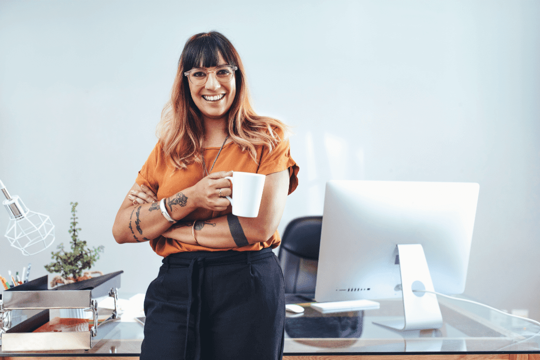 woman holding coffee standing in front of desk in office