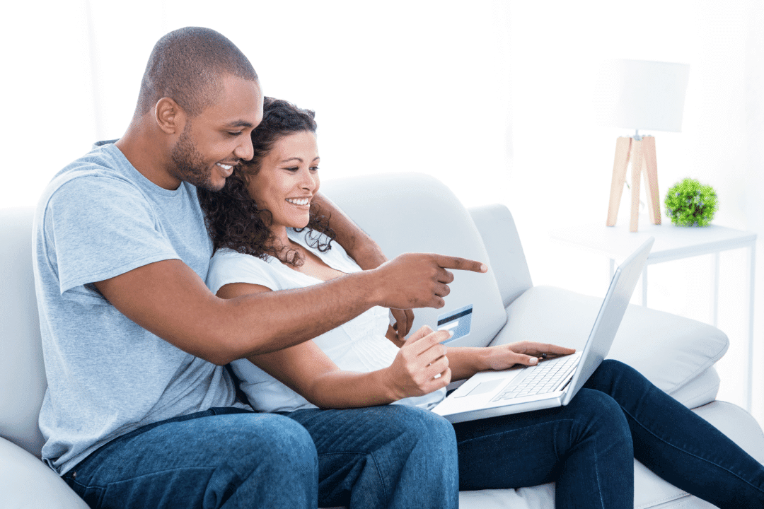 couple online shopping on sofa using credit card