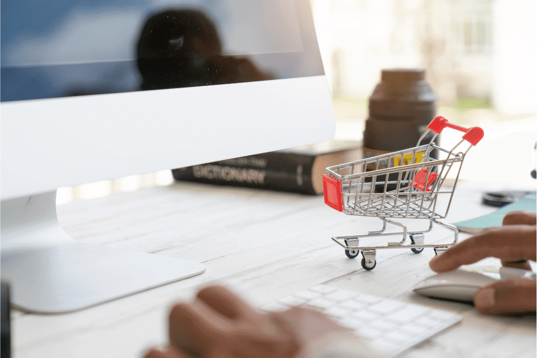 online shopping miniature cart on desk with desktop computer