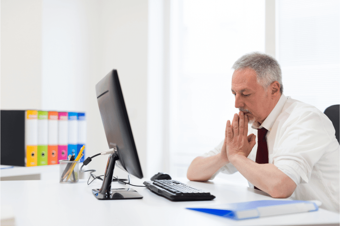 older man looking frustrated while looking at computer screen in office