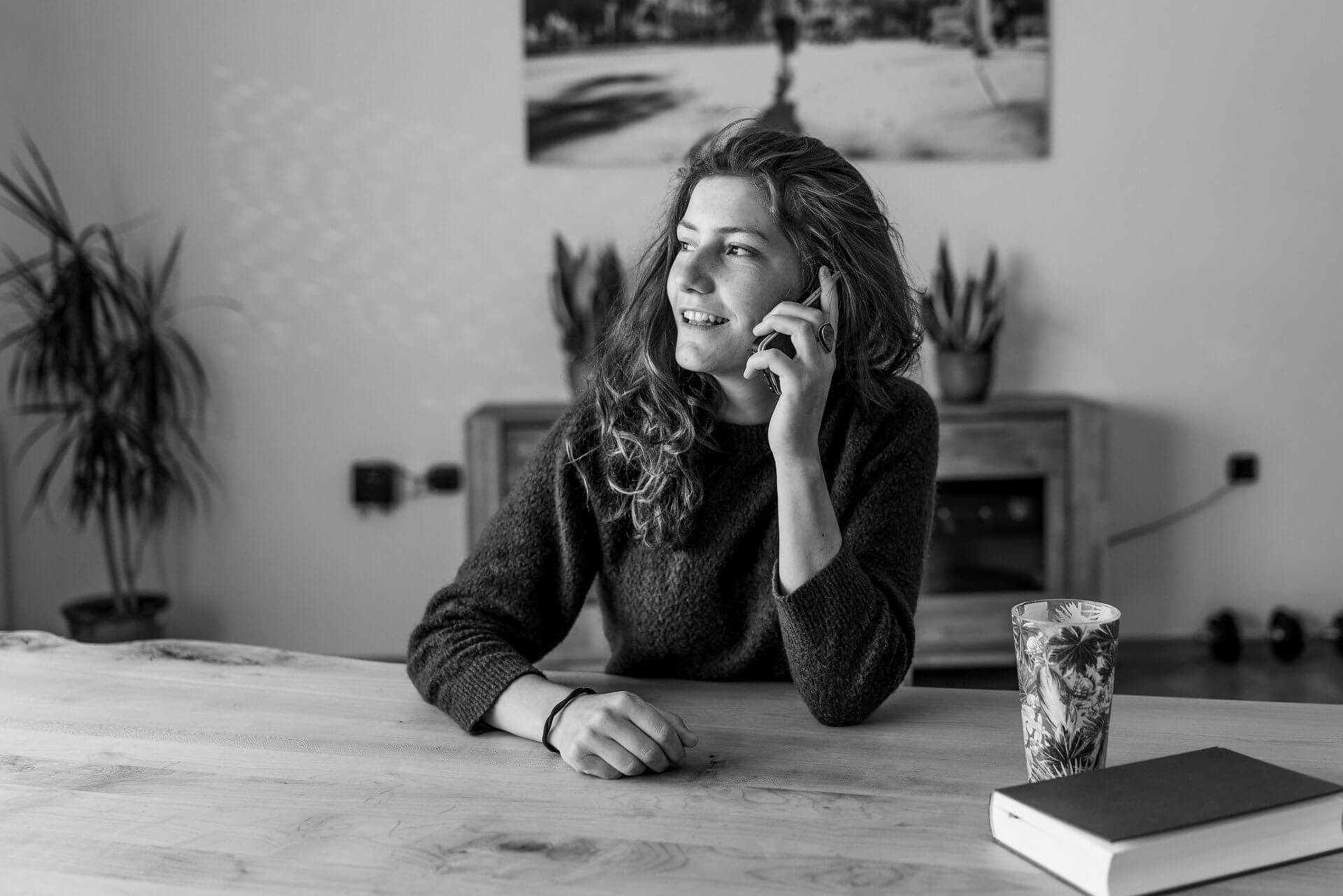 woman sitting at a table on the phone