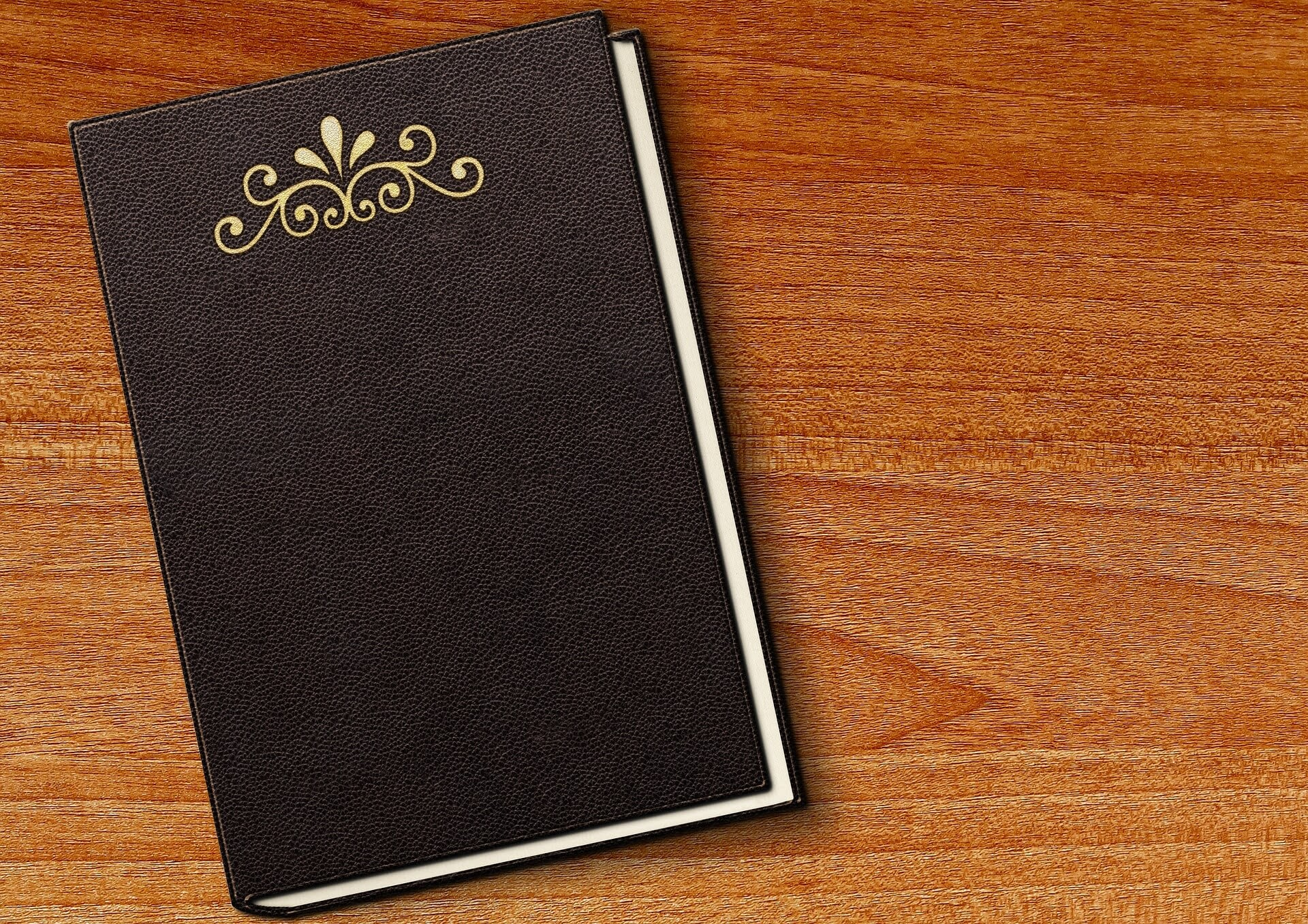 closed black book with embossed cover on a table