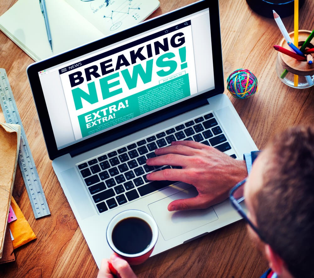 "computer screen showing a ""Breaking News"" headline"