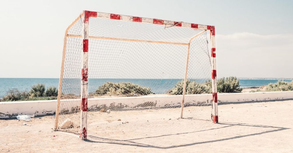 Red and white goal posts with net on a beach in front of ocean