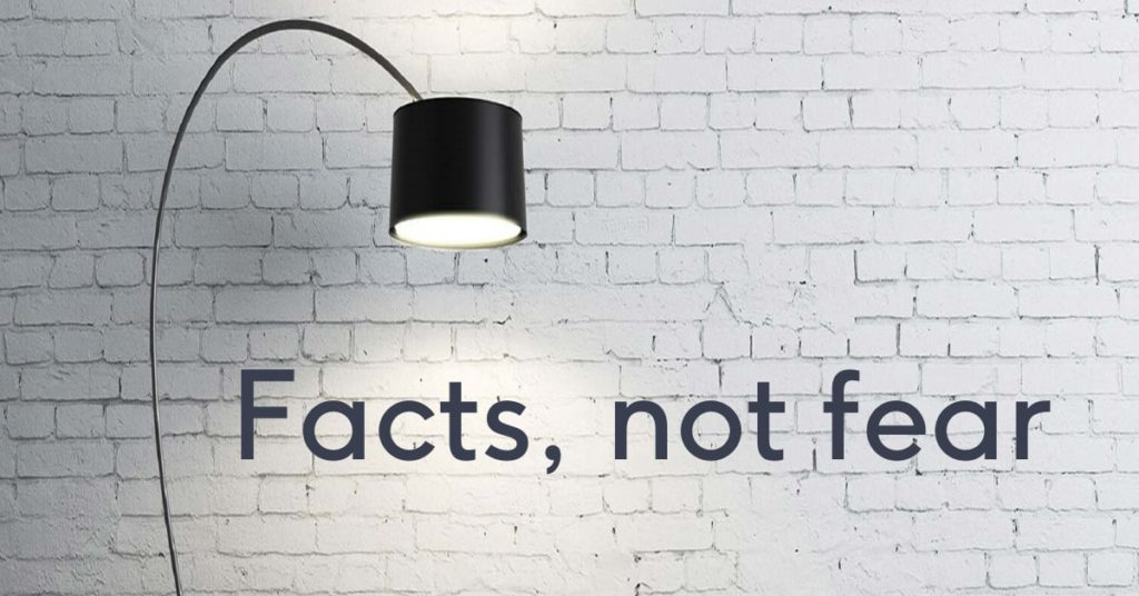 White brick wall with lamp shining on the words fact not fear