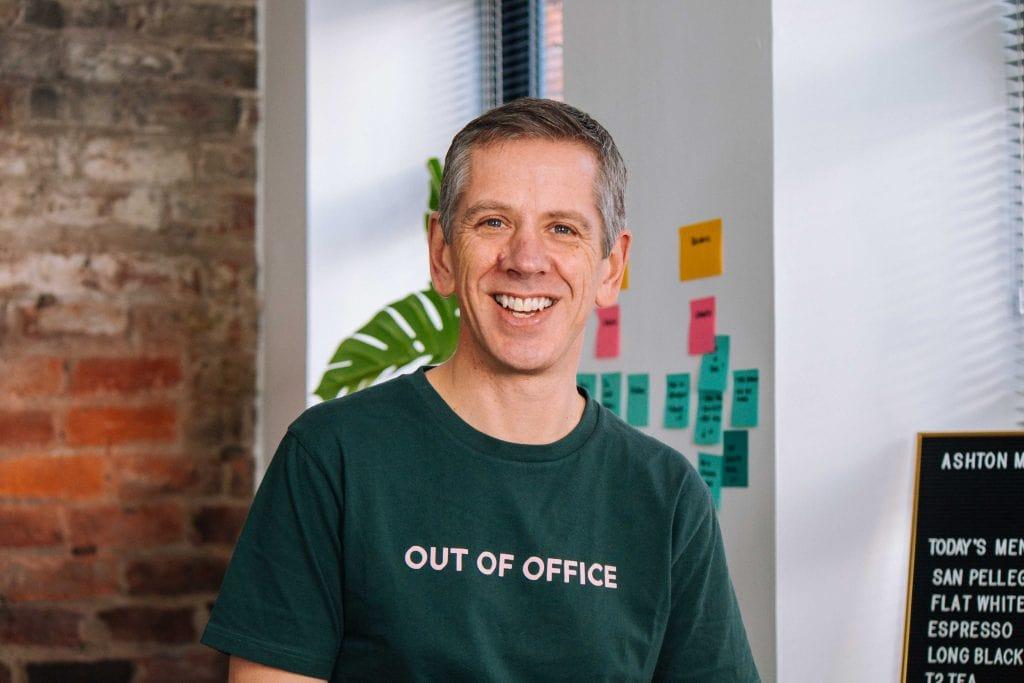 Headshot of white man in green t shirt smiling