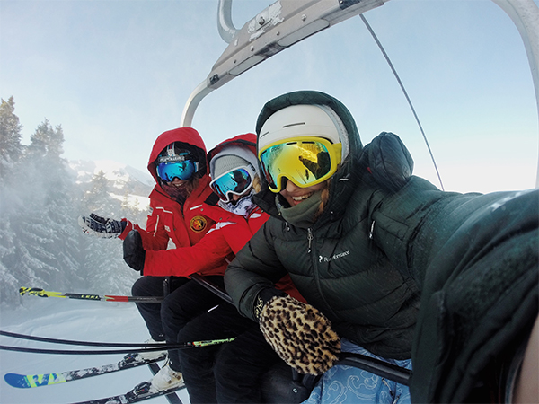 Three skiers riding a chairlift.