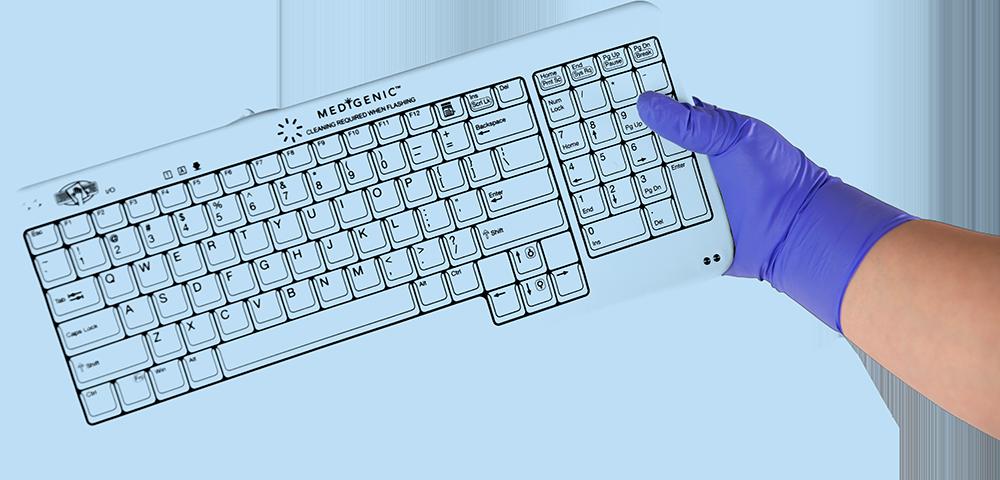 Gloved hand holding a Medigenic washable keyboard.