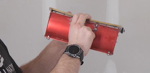 Inspecting trowel bar flexibility on a LEVEL5 Tools drywall flat box.