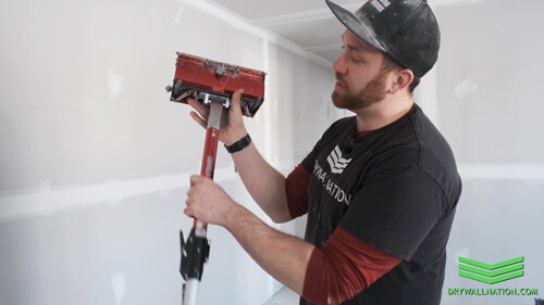 Drywall Nation showing how to carry red LEVEL5 drywall flat box and short extension handle.
