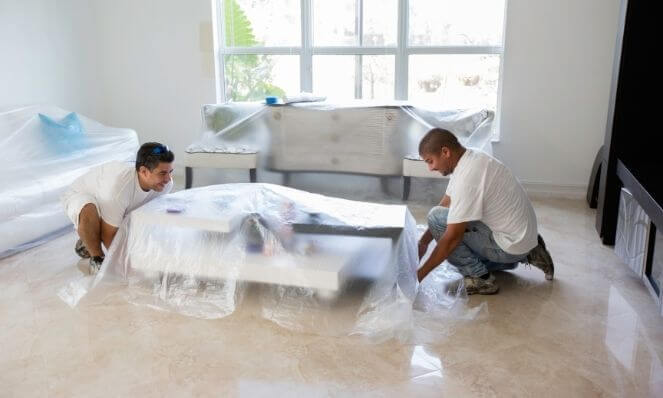 A team applying plastic cloths to furniture to protect it from dust and debris when prepping to remove popcorn ceiling texture.