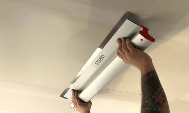 A LEVEL5 32-Inch Drywall Skimming Blade applying a skim coat to a ceiling.
