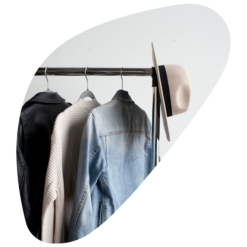 leather jacket, cream sweater, jean jacket, and hat on a clothing rack.