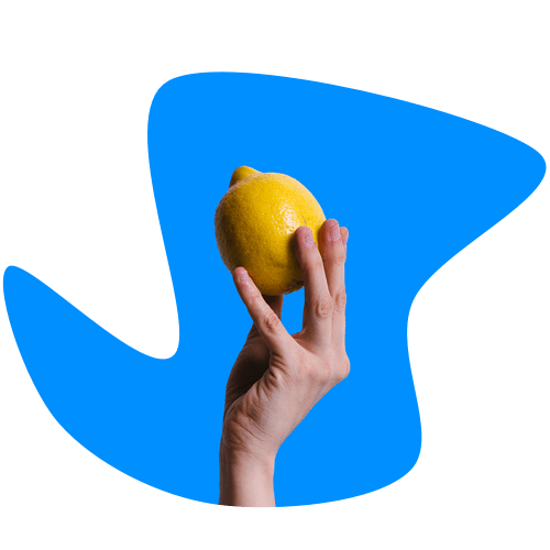 A hand holding a lemon on a blue background