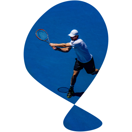 Male swinging a tennis racket on a blue tennis court.