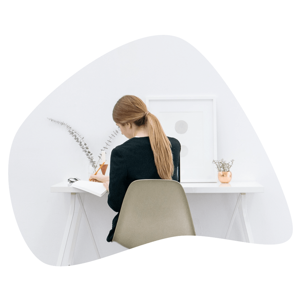 Female sitting with her back towards us while working at a white desk.