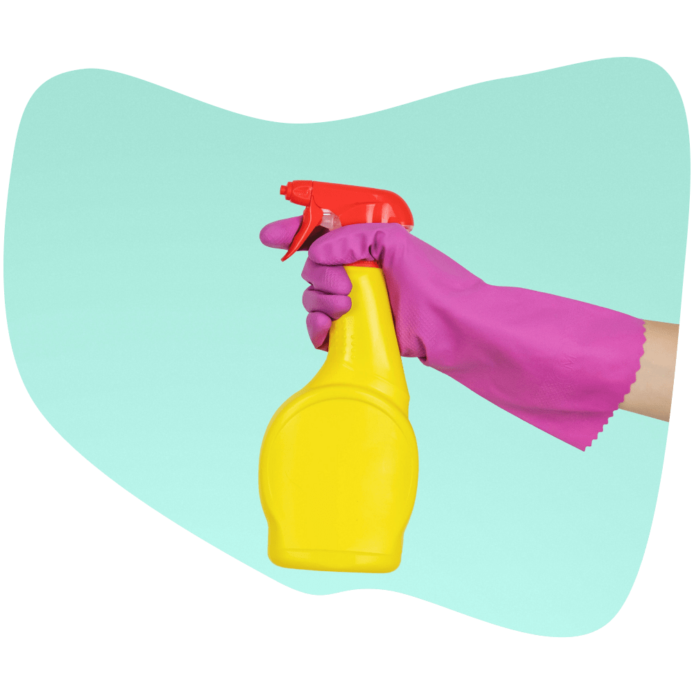 A hand wearing a purple glove holding a yellow spray bottle with a red cap.