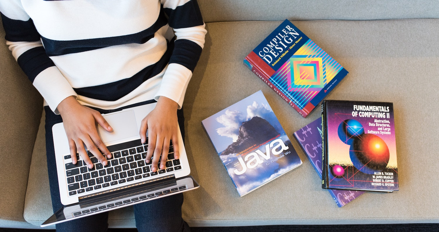 Freelancer on laptop with manuals and books next to them