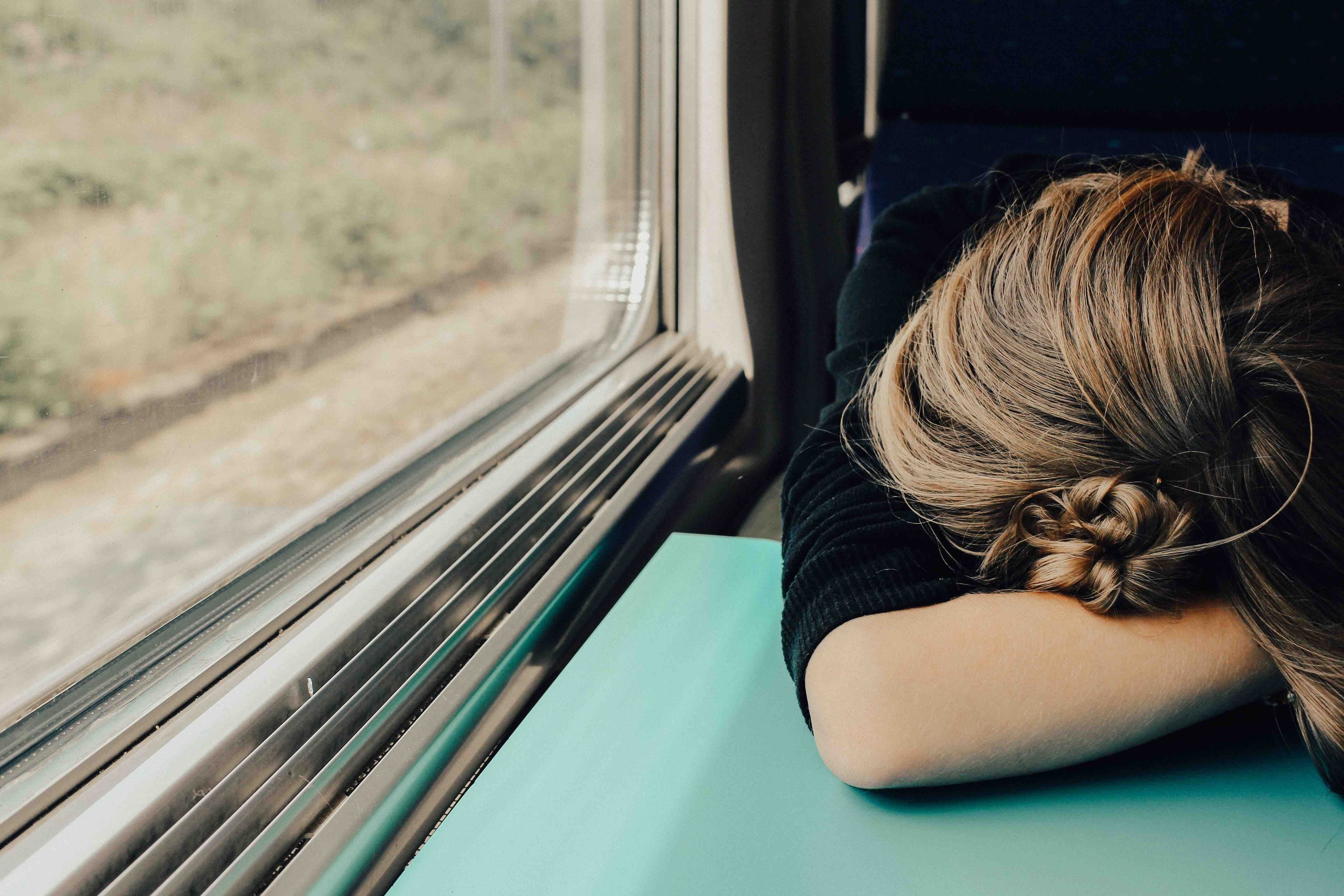 woman experiencing burnout on train