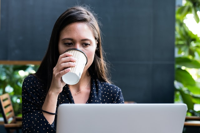 Woman sipping coffee at a computer doing task automation