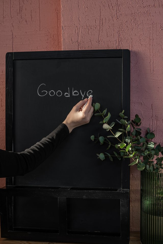 "Person writing ""goodbye"" on a chalkboard, signifying firing a client"