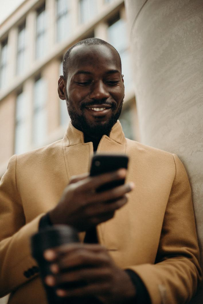 Freelancer looking at phone, receiving message from new client who just came to him from his business development efforts