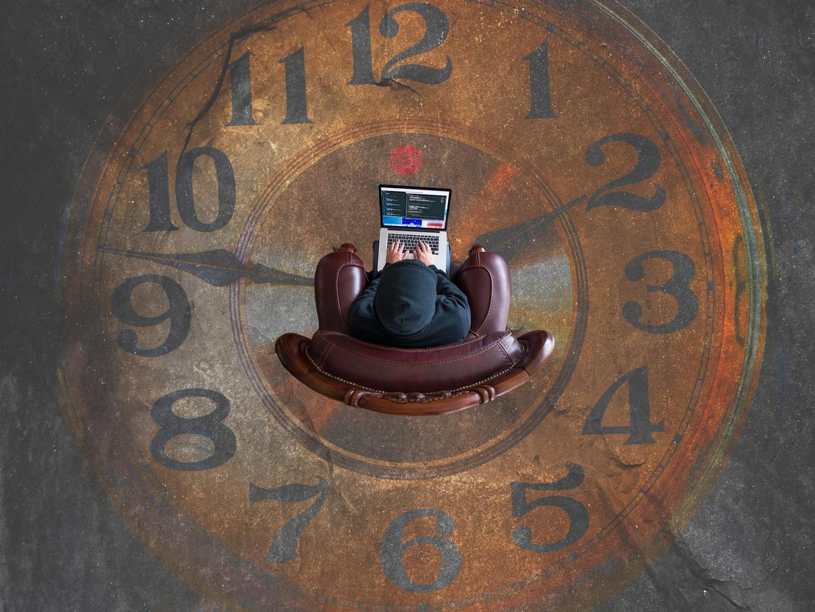 A freelancer types furiously on a computer trying to meet a deadline, while surrounded by a ticking clock.