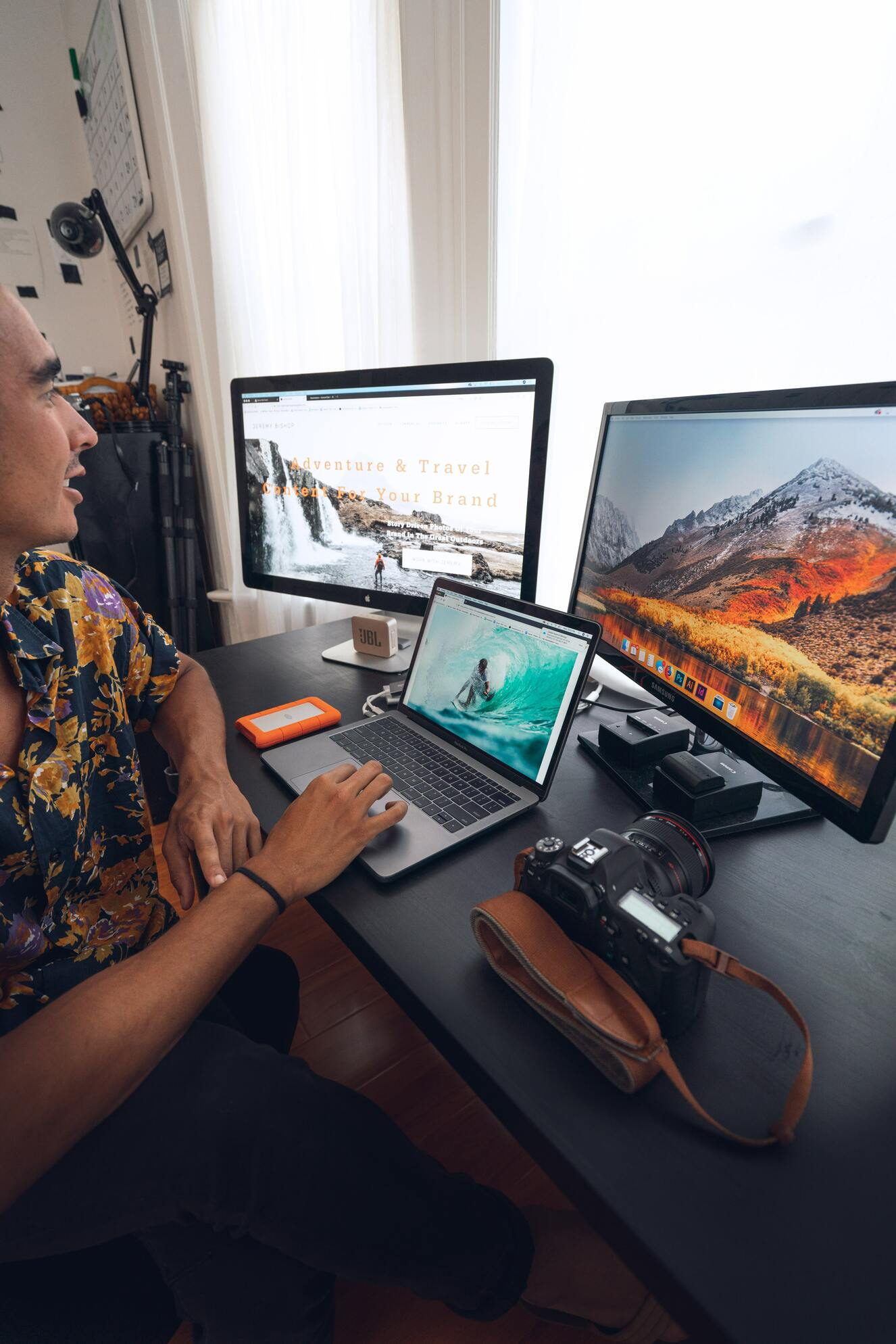 Freelance Photographer Managing Projects On Multiple Screens