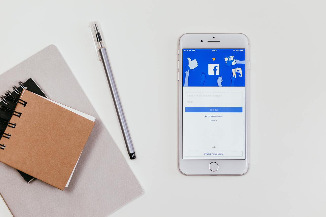 Freelance digital marketer has Smartphone with Facebook on the screen sits