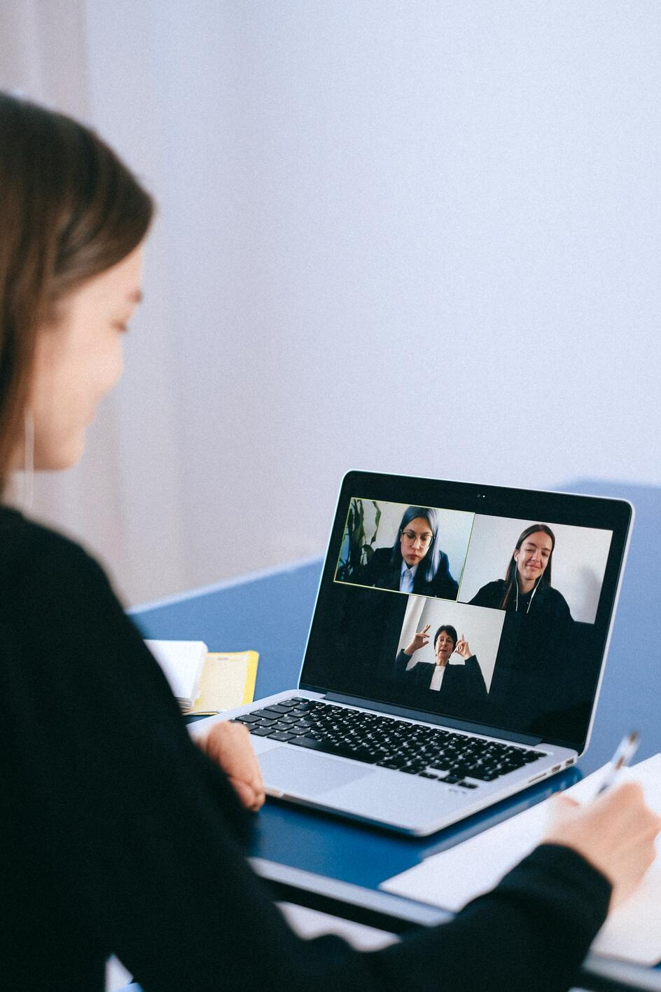 Freelance project manager having a video meeting with the project team on her laptop
