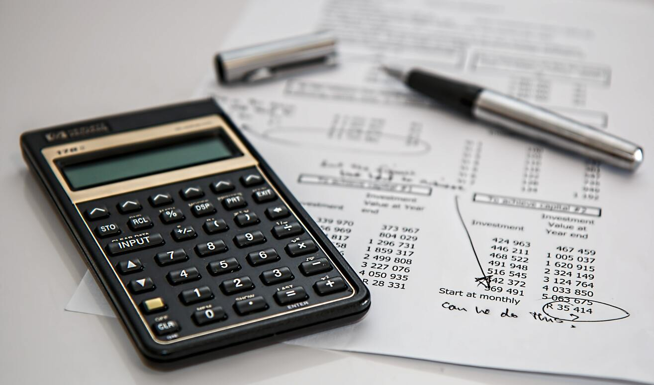 Financial statement with calculator and pen used to calculate business finances