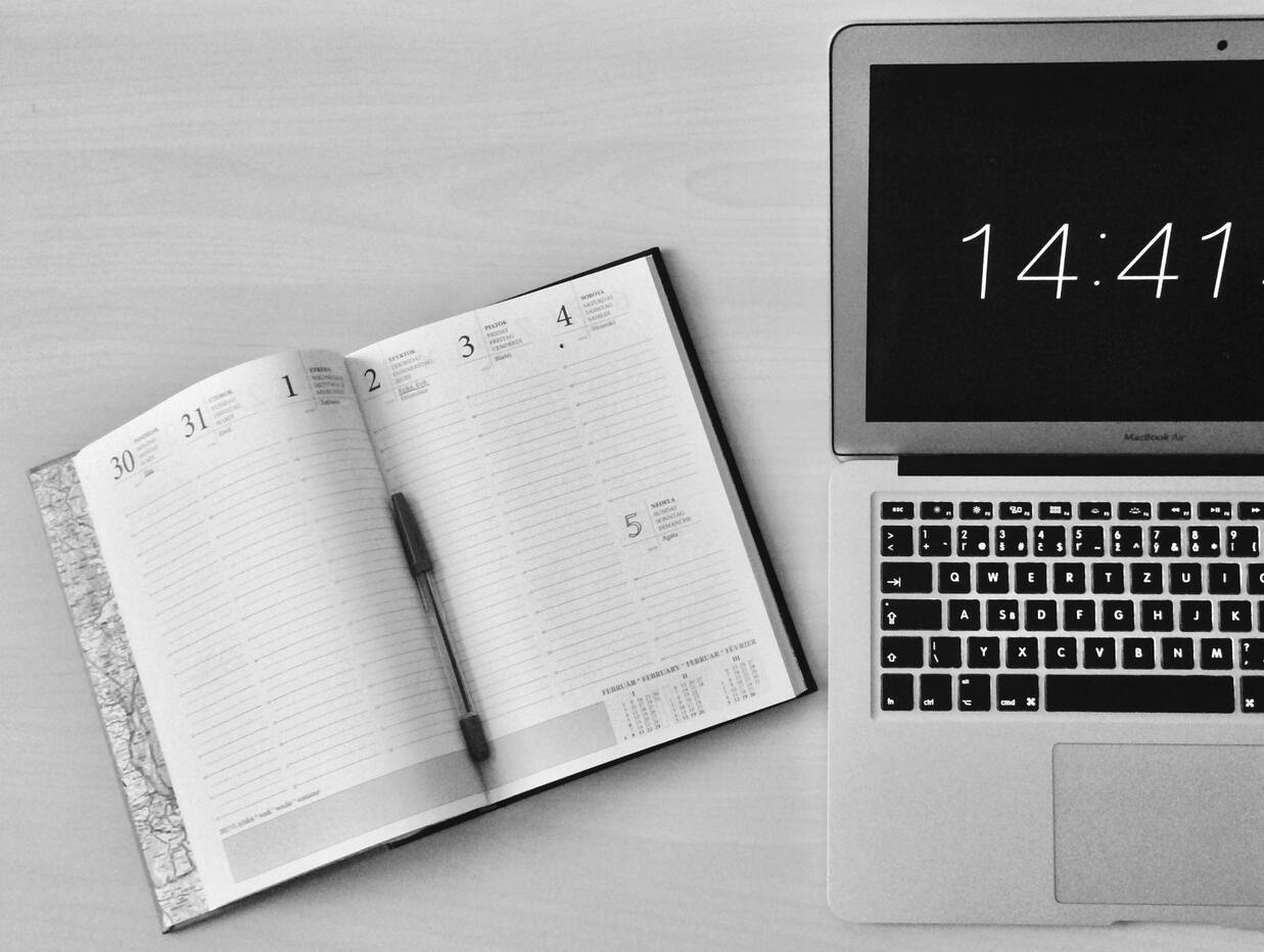 Laptop with a timer sitting on a table next to a day planner