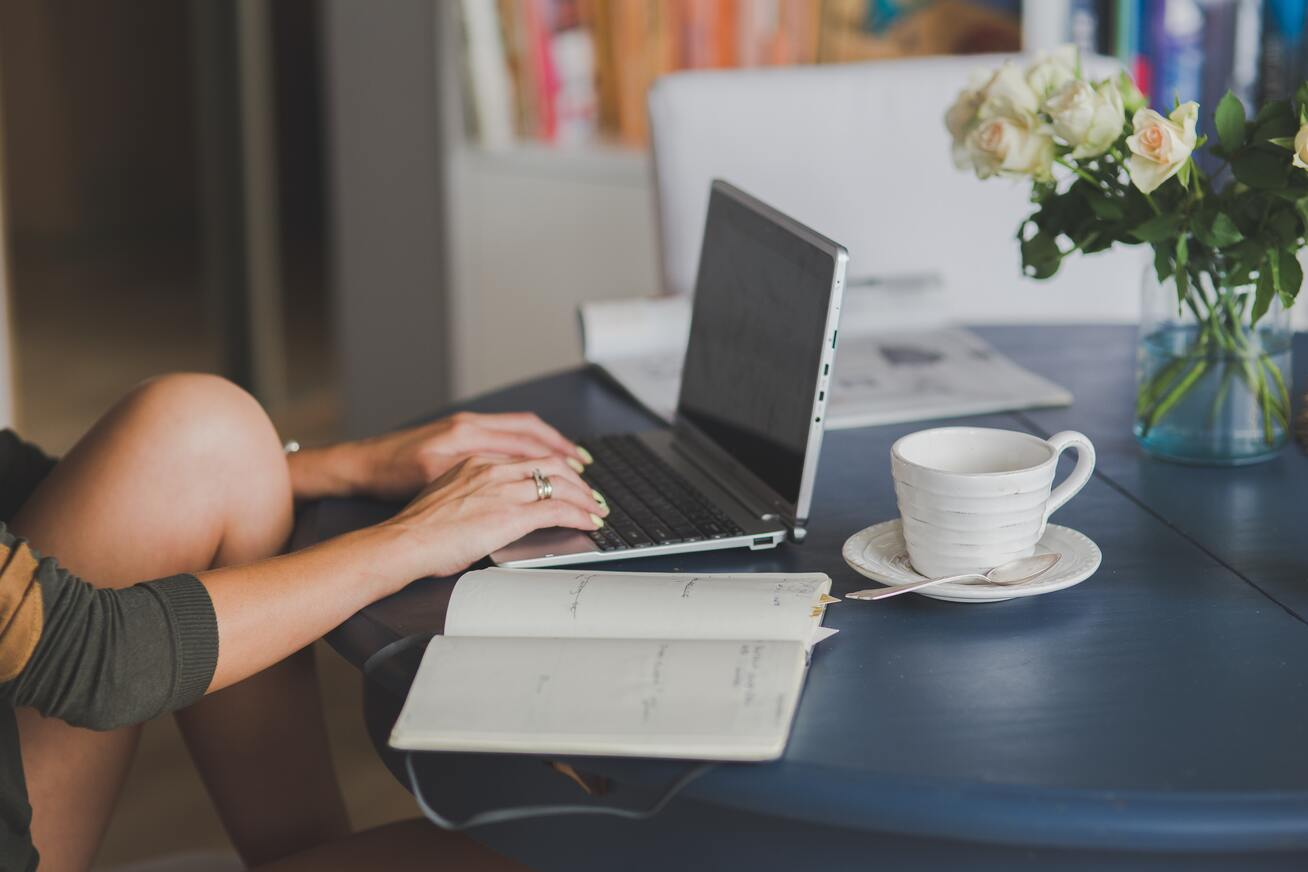 Freelancer using laptop while sitting at a table with a notebook and coffee mug
