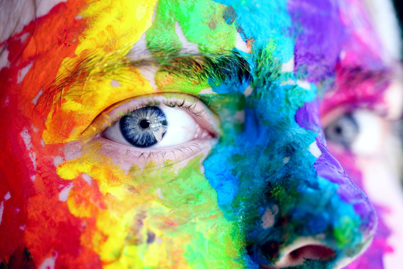 A creative with blue eyes stares ahead with colorful paint covering her face.