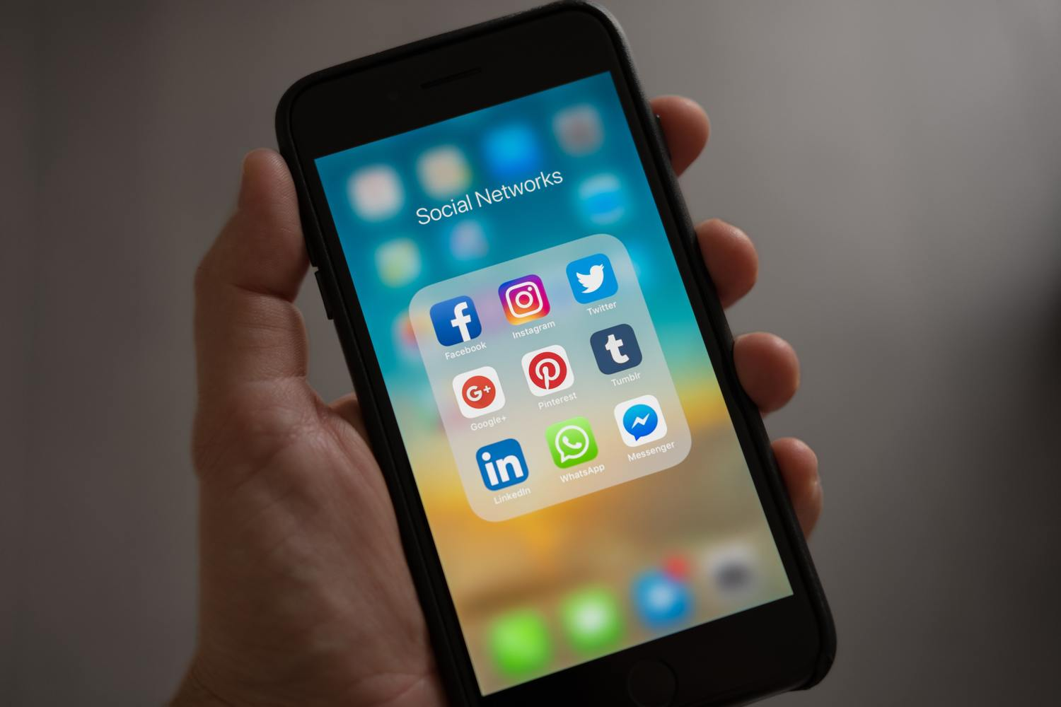 A social media manager holds a phone displaying all the different social platforms.