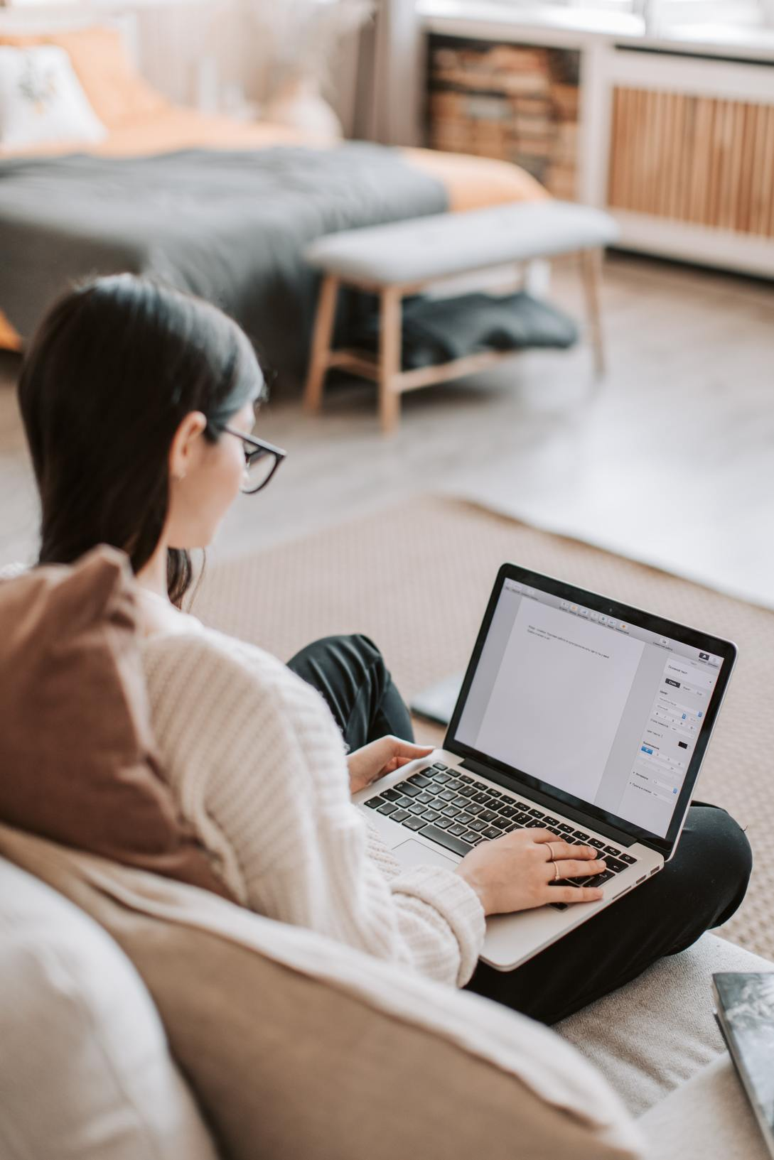 Woman sitting on a couch writing a marketing strategy