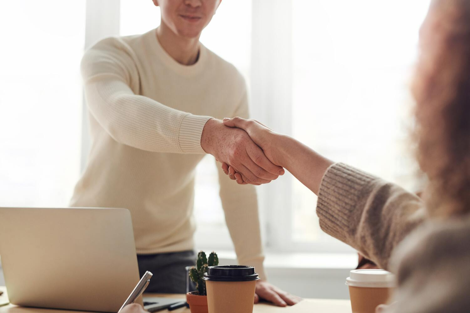 Two copywriters shake hands in an office after being hired