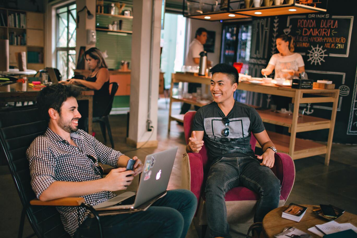 Two freelancers chatting while working at a coffee shop